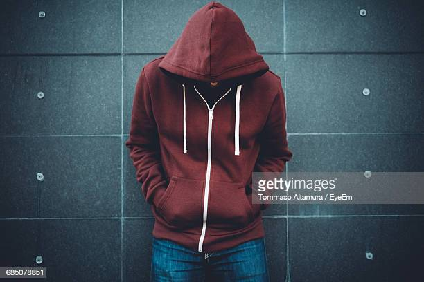 upset man standing against gray wall - hooded shirt stock pictures, royalty-free photos & images