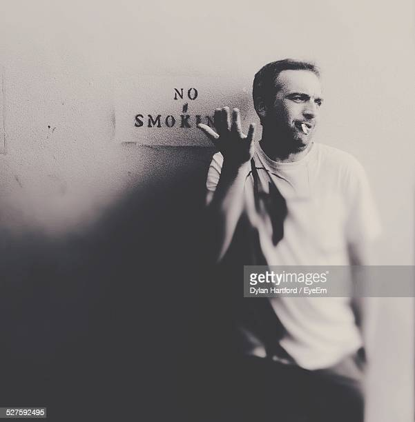 Upset Man Standing Against No Smoking Sign On Wall