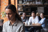 Upset mixed race woman suffering from bullying, sitting alone in cafe