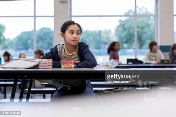 écolière bouleversée mangeant seule - cantine photos et images de collection