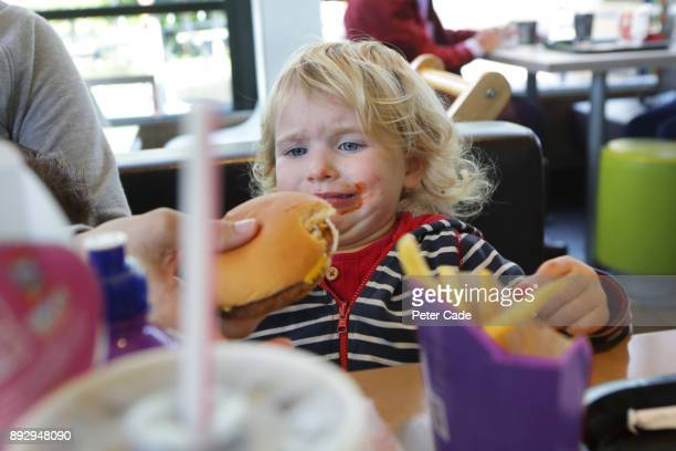 Upset toddler being given burger in fast food restaurant