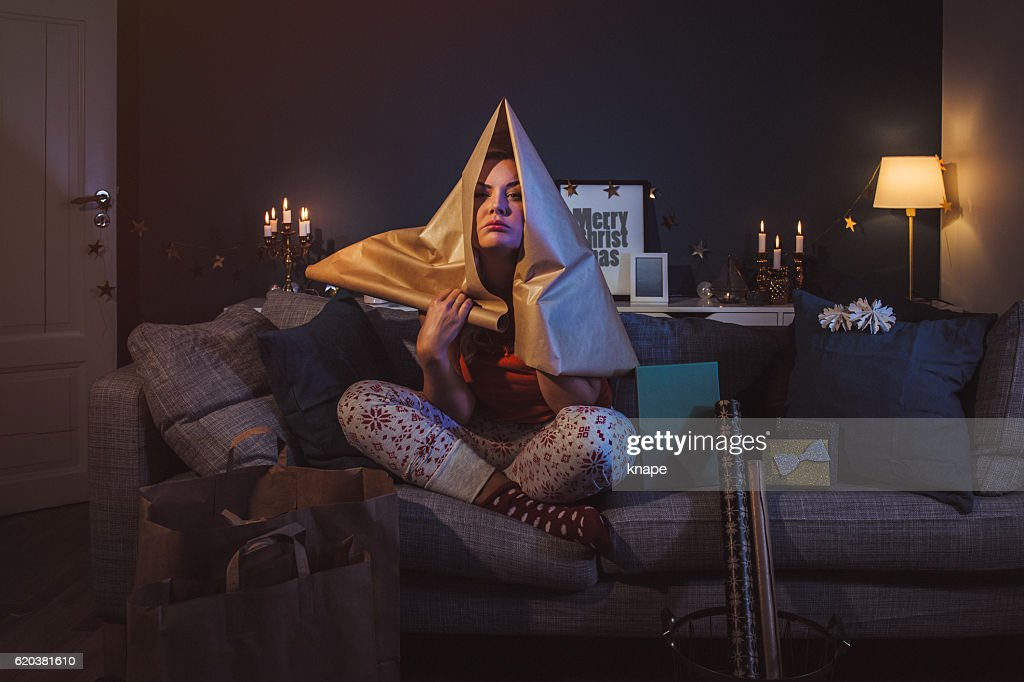 Upset woman at home with christmas gifts : Stock Photo