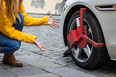 Upset woman looks at her parked car with wheel clamp.