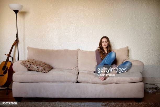 upset woman sitting on sofa at home - sitting stock pictures, royalty-free photos & images