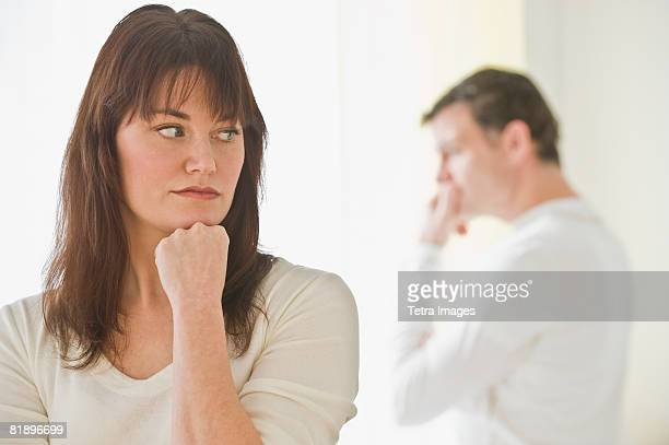 Upset woman with husband in background