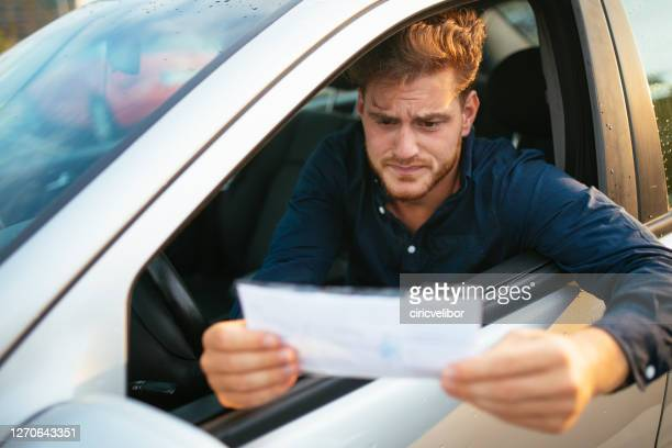 upset young man gets parking ticket - wikipedia:citation stock pictures, royalty-free photos & images
