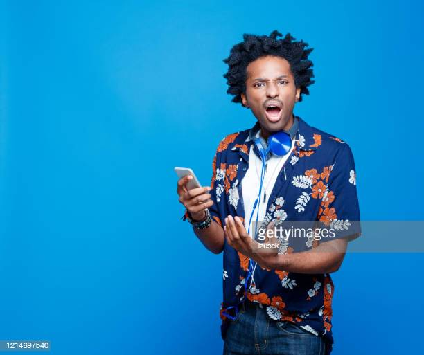 upset young man in hawaiian shirt holding smart phone - anger stock pictures, royalty-free photos & images
