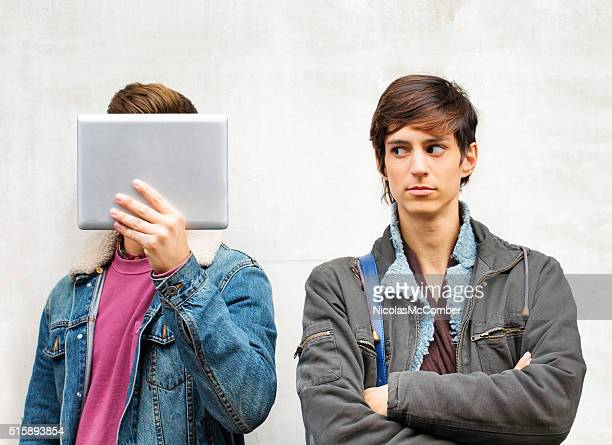 Upset young woman annoyed by male friend hiding behind tablet