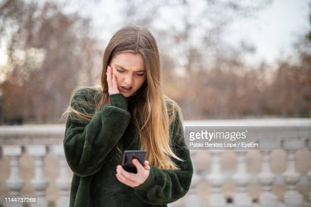 upset young woman using mobile phone while standing in park during winter - reizen stock-fotos und bilder