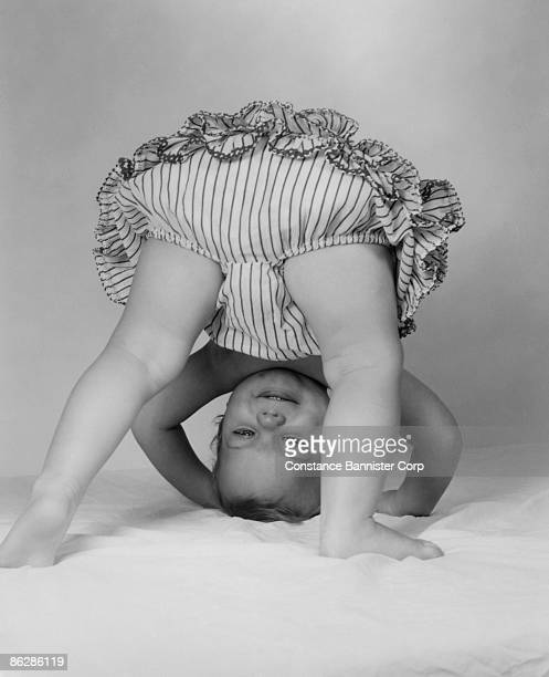 upside down baby looking through legs - little girls bent over stock photos and pictures
