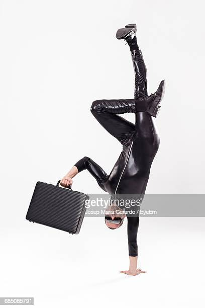 upside down burglar wearing latex holding briefcase against white background - latex stock pictures, royalty-free photos & images