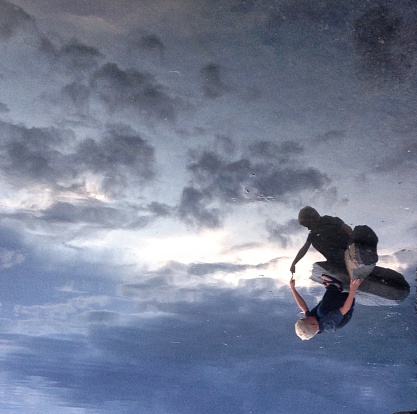 Upside Down Image Of Boy Touching Reflection In Lake - gettyimageskorea