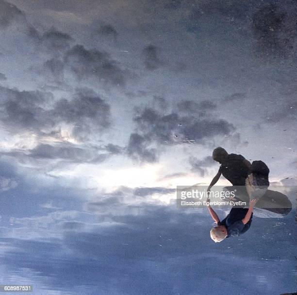 upside down image of boy touching reflection in lake - op z'n kop stockfoto's en -beelden