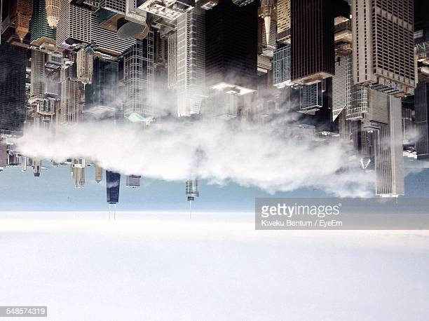 Upside Down Image Of Cityscape Against Cloudy Sky