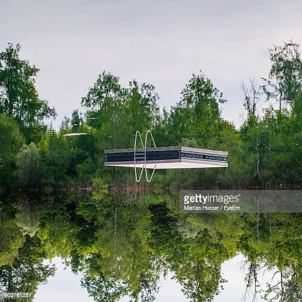 Upside Down Image Of Diving Platform And Trees Reflecting In Lake