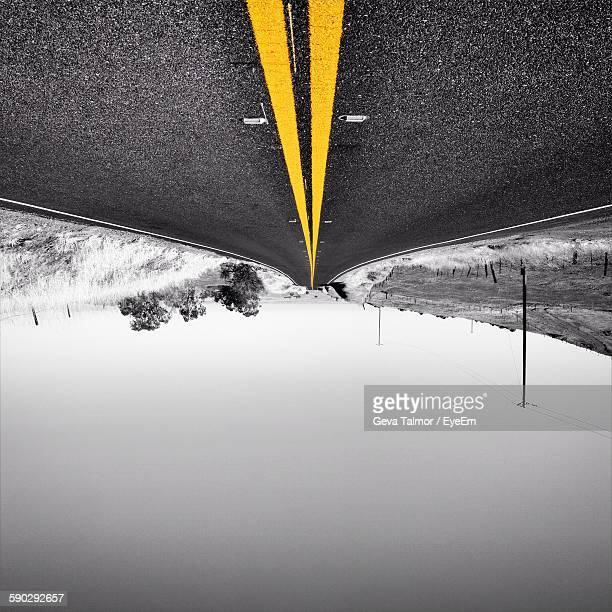 Upside Down Image Of Double Yellow Lines On Road Against Sky