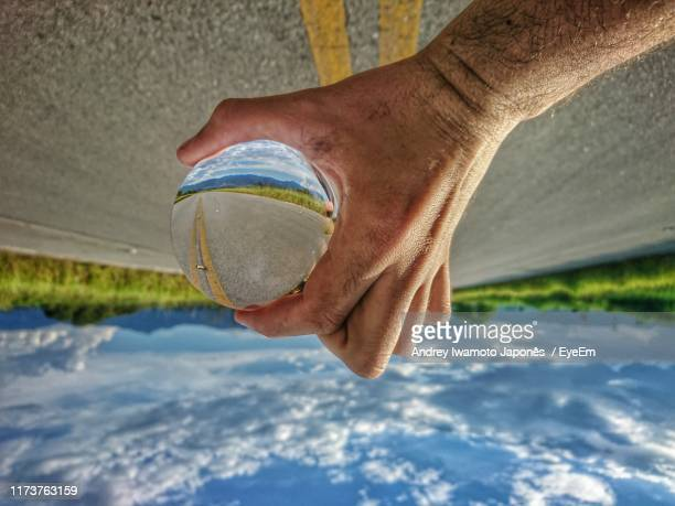 upside down image of man holding crystal ball against road - japonês stock pictures, royalty-free photos & images