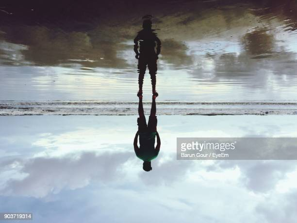 upside down image of man standing at beach against cloudy sky - op z'n kop stockfoto's en -beelden