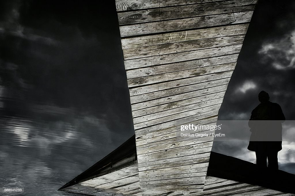 Upside Down Image Of Man Standing On Pier With Reflection In Lake : Stock Photo