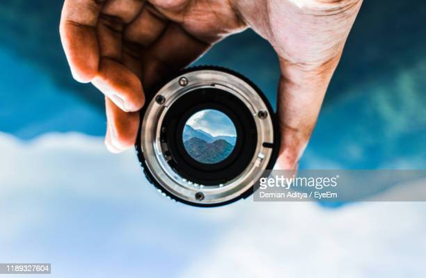 upside down image of person holding camera lens against mountain - image focus technique stock pictures, royalty-free photos & images