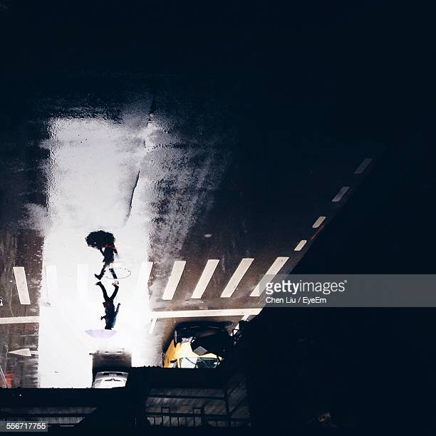 Upside Down Image Of Person Walking On Wet City Street