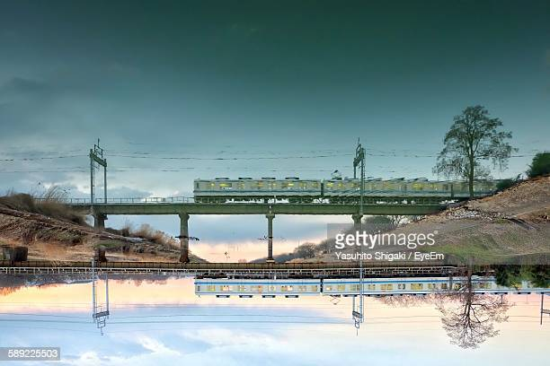 upside down image of train on bridge with reflection in lake - 埼玉県 ストックフォトと画像