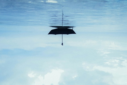 Upside Down Image Of Umbrella Floating On Sea Against Sky - gettyimageskorea