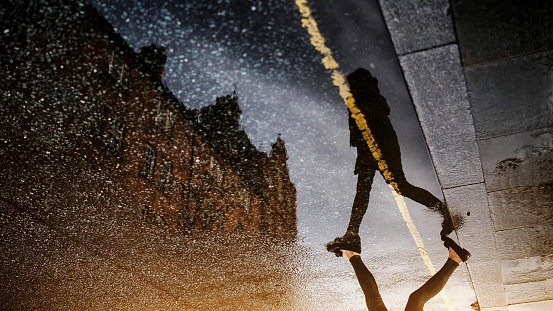 Upside Down Image Of Woman Walking Street With Reflection In Puddle - gettyimageskorea
