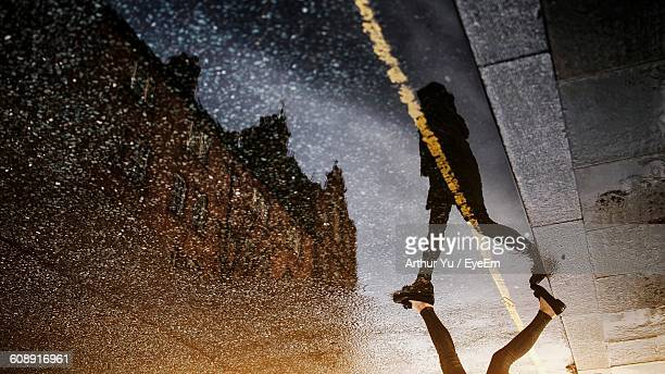 upside down image of woman walking street with reflection in puddle - spiegelung stock-fotos und bilder