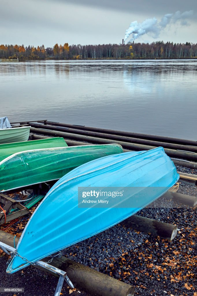 Upside down, overturned green and blue boat on the river banks of the Oulujoki River, Oulu, Finland : Stock Photo