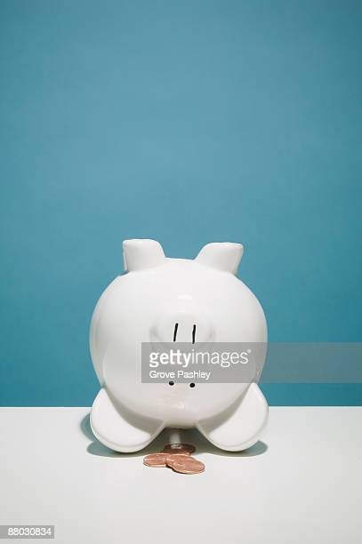 Upside down piggy bank with pennies