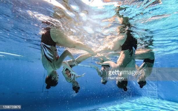 ondersteboven gesynchroniseerde zwemmers die een choreografiepraktijk doen - match sport stockfoto's en -beelden