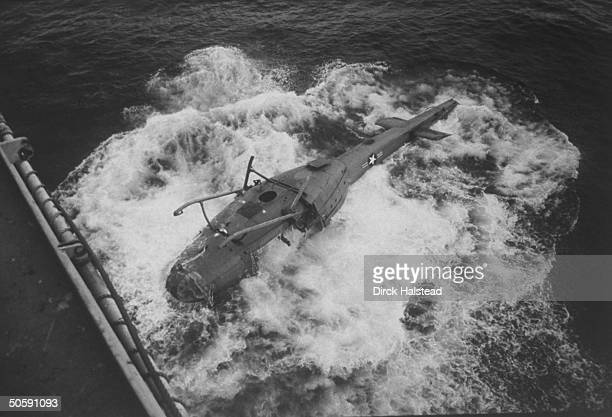 Upside-down US military helicopter being ditched in the S. China Sea from the USS Blue Ridge after final evacuation from Vietnam.