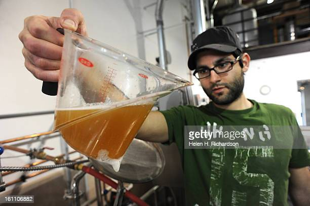 Upslope Brewing Company lead brewer Yazan Karadsheh checks the clarity and color of the beer that he took out of the mash tank A bill to allow...