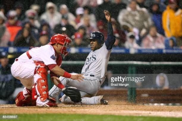 J Upton of the Tampa Bay Rays slides into home plate to score the tying run in the top of the sixth inning during game five of the World Series...