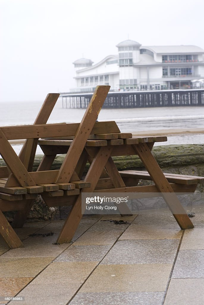 Upturned wooden tables at out of season seaside : Stock Photo