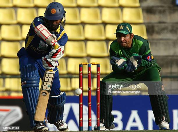 Upul Tharanga of Sri Lanka bats as Pakistan wicketkeeper Sarfraz Ahmed looks on during the first one day international match between Sri Lanka and...