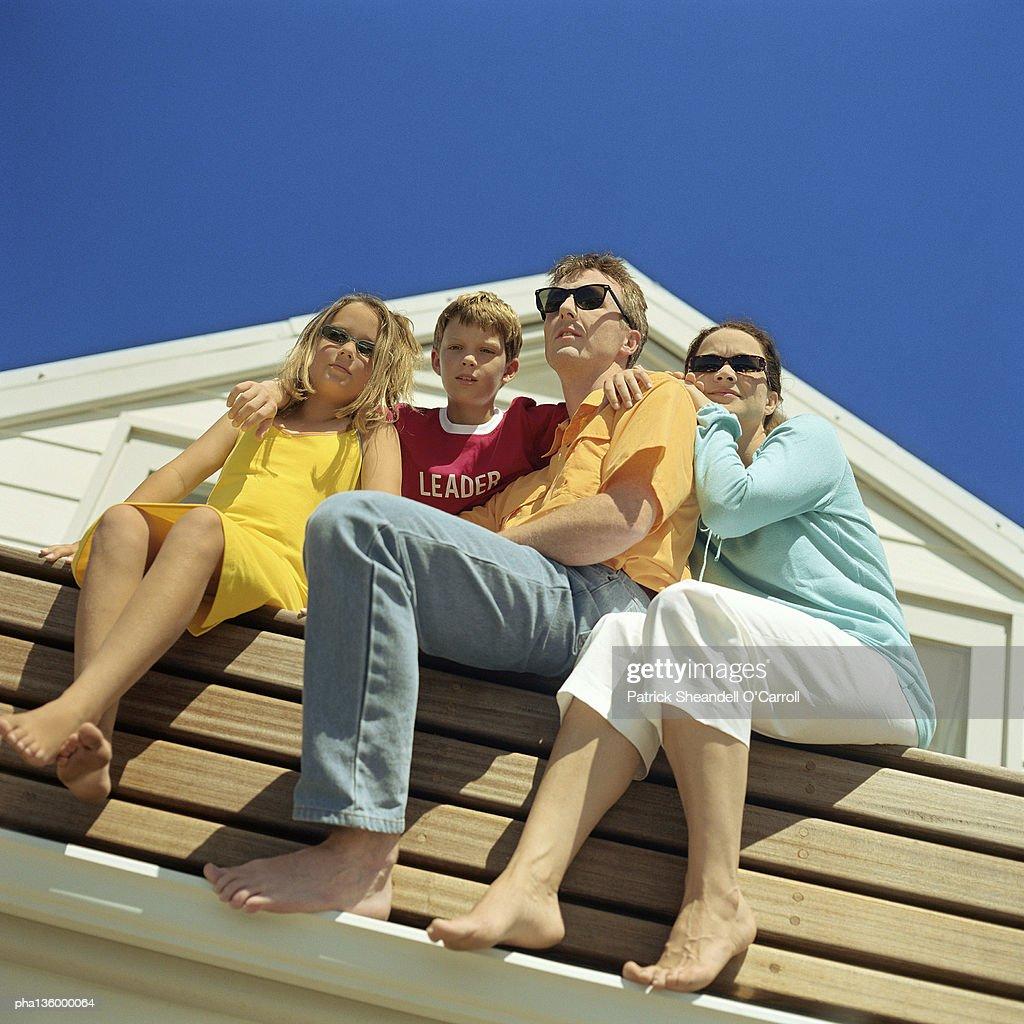 Upward angled shot of family sitting on bench, all wearing sunglasses : Stockfoto