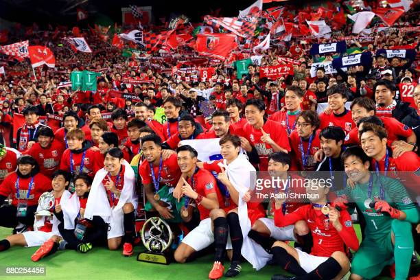 Urawa Red Diamonds players pose for photographs with supporters after winning the AFC Champions League Final second leg match between Urawa Red...
