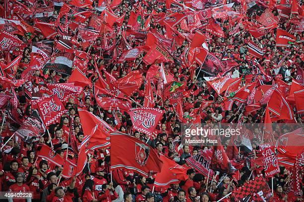 Urawa Red Diamonds supporters wave flags prior to the JLeague match between Urawa Red Diamonds and Gamba Osaka at Saitama Stadium on November 22 2014...