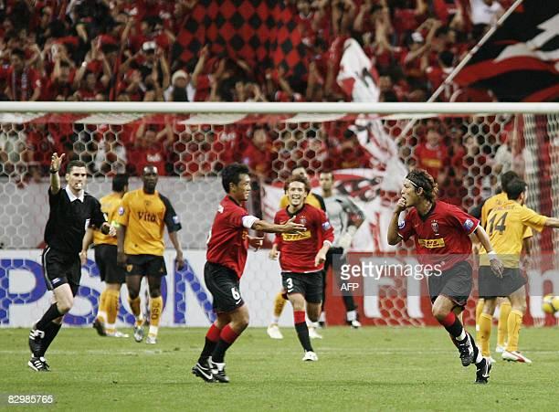 Urawa Reds midfielder Takahito Soma of Japan runs to his teammate Nobuhisa Yamada as Hajime Hosogai looks on after scoring against Al Qadsia of...