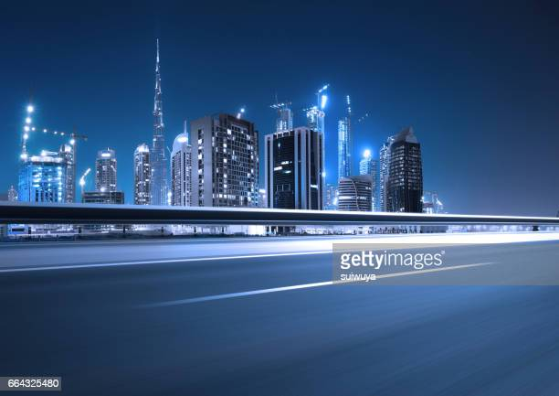 Urban asphalt road with dubai skyline background at night