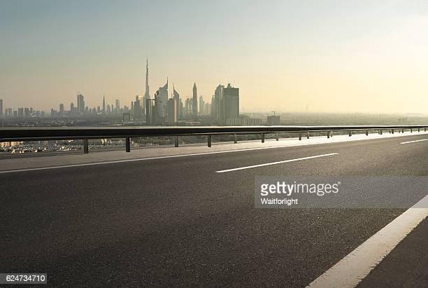 Urban asphalt road with dubai skyline background