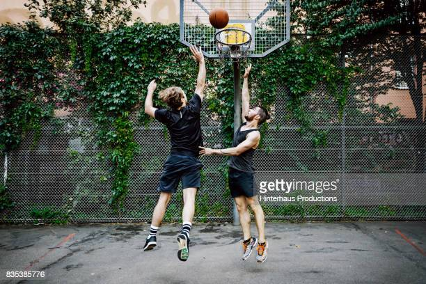 urban basketball player jumps to make shot during friendly game - basketball stock-fotos und bilder
