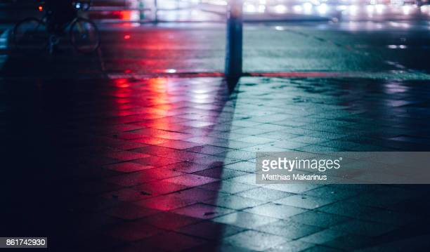 urban city street night lights with reflection and a bicycle - licht stock-fotos und bilder