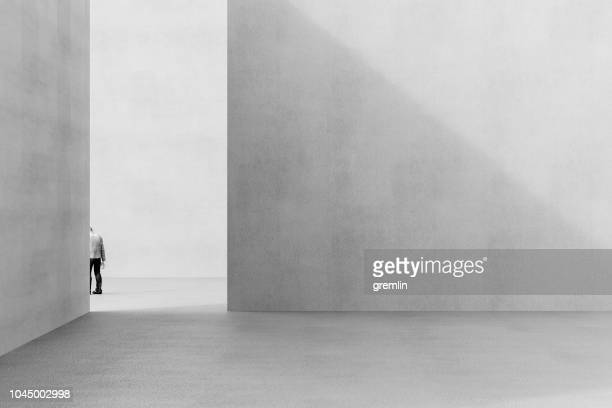 urban concrete environment with sad businessman leaving - arquitetura imagens e fotografias de stock