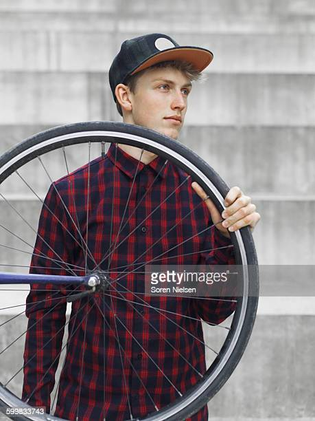Urban cyclist carrying tyre in front of steps