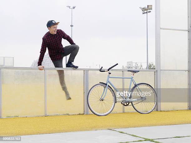Urban cyclist climbing over fence on sports field