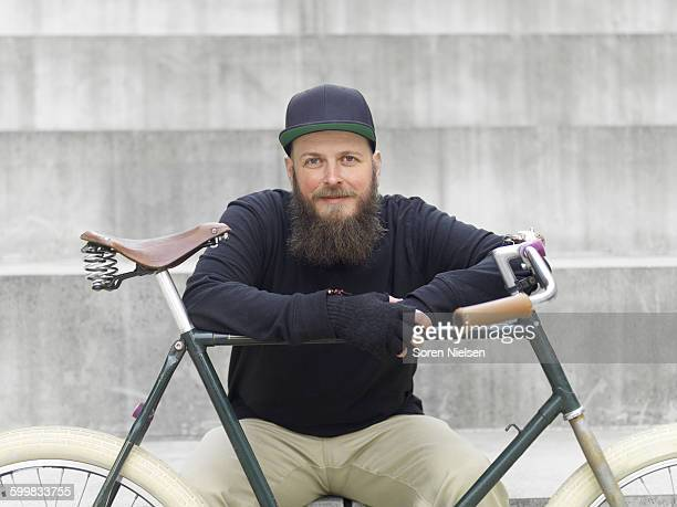 Urban cyclist on steps leaning on bicycle