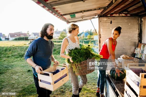 urban farmers loading truck with freshly harvested goods for market - ernten stock-fotos und bilder